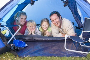 Families Camping In Tent Smiling