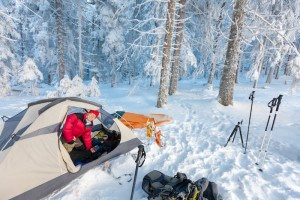 Woman inside tent set in winter forest