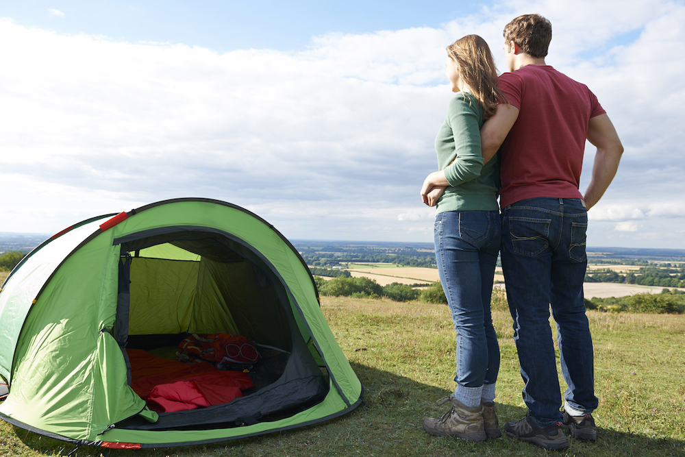 Couple Camping In Countryside Standing By Tent
