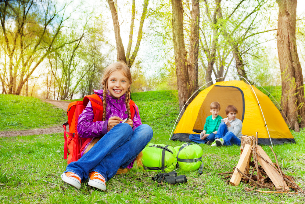 Happy girl with notebook and kids relaxing near the wooden bonfire and yellow tent during camping in summer weather
