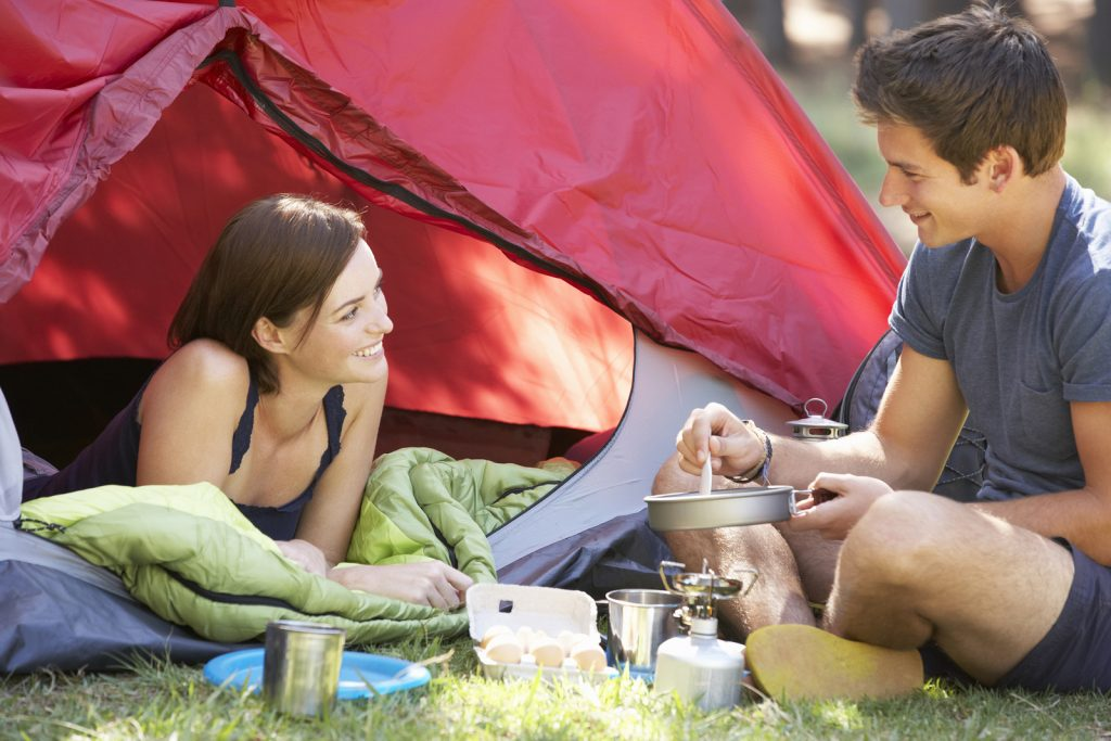 Young Couple Cooking Breakfast On Camping