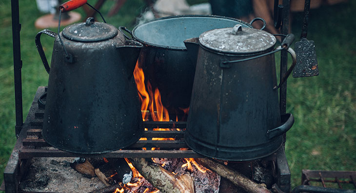 two kettles cooking on a campfire