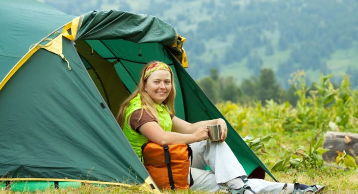 happy female camper sitting outside her tent