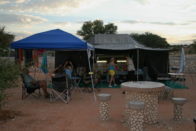 a small family gathering under a canopy tent