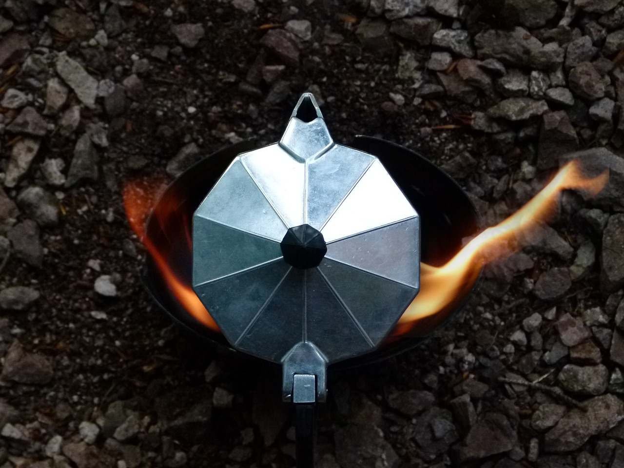 camping coffee maker placed in a fire