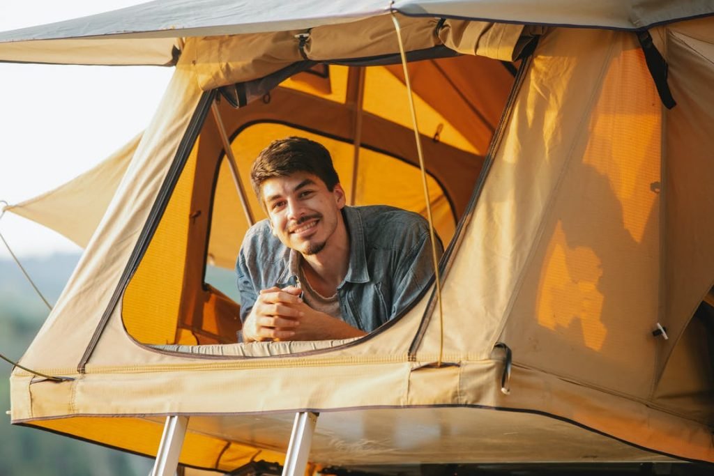 man wearing grey button-up smiling inside of canvas tent