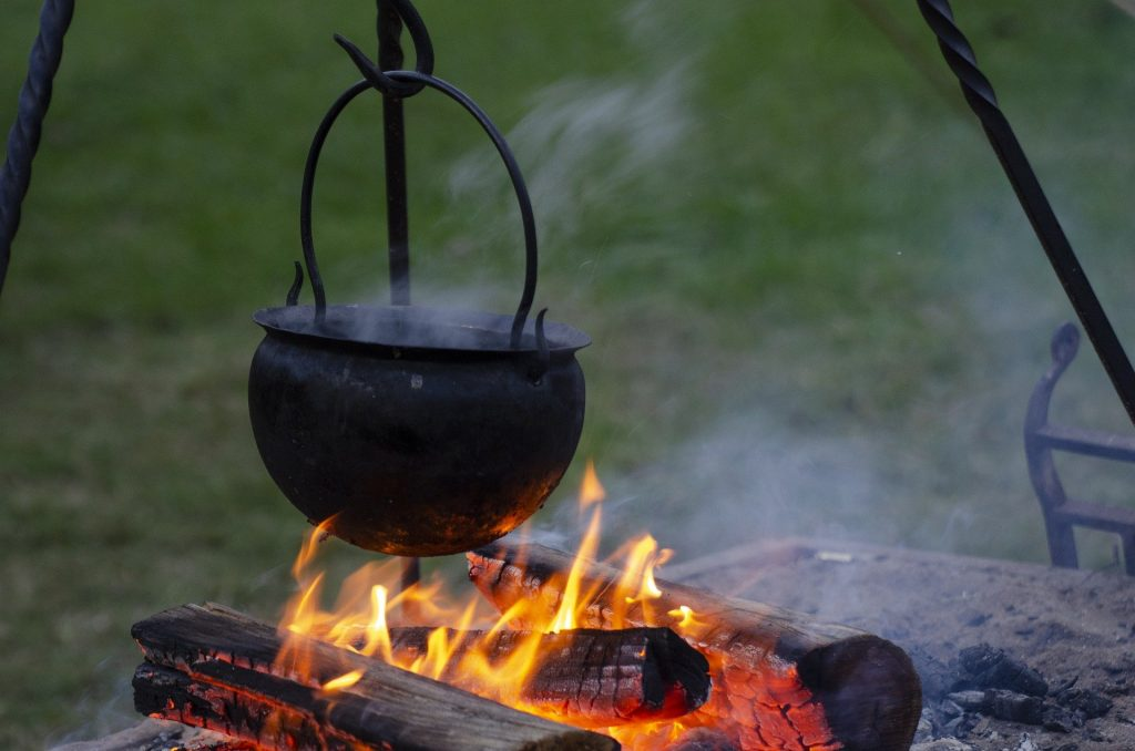 A cast iron pot hanging over a campfire